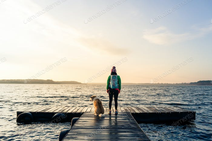 Woman with dog enjoy sunrise at lake, backpacker