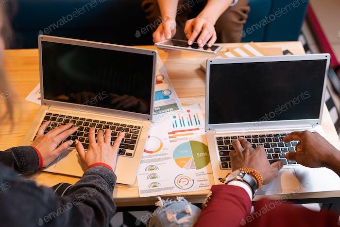 Hands of intercultural students pressing keys of laptop keypads