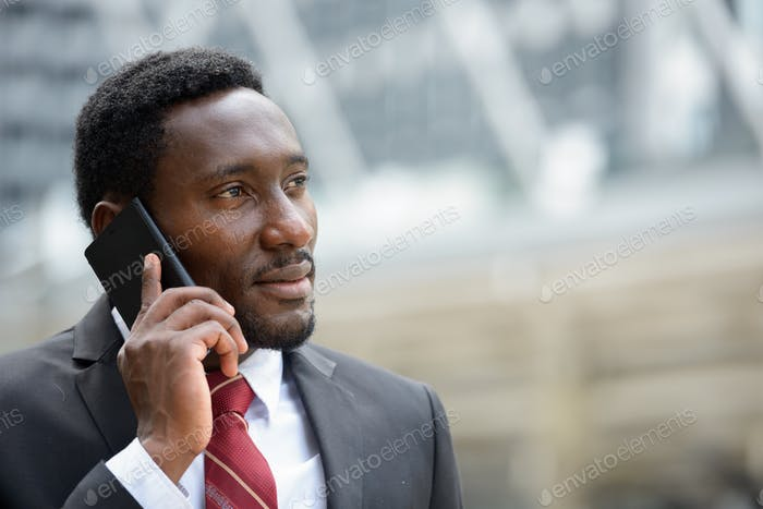 Young handsome African businessman talking on mobile phone