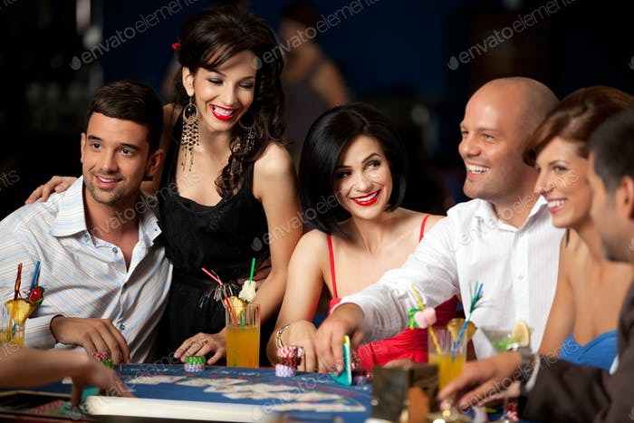 laughing friends playing cards in casino