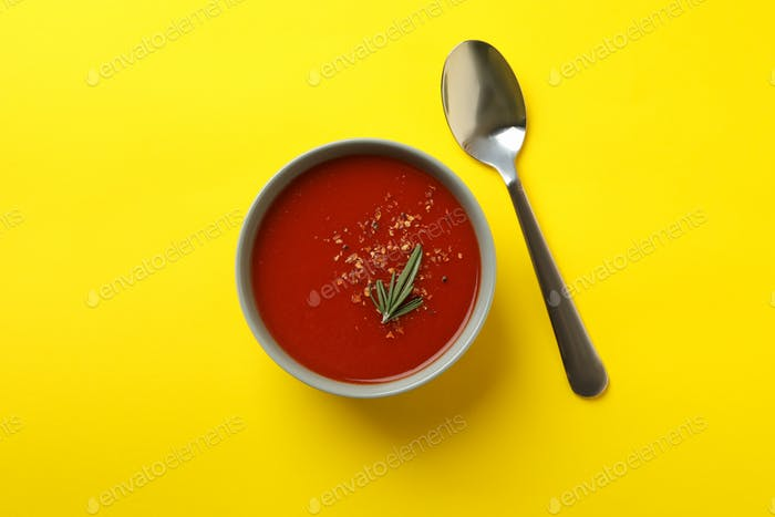 Bowl of tasty tomato soup and spoon on yellow background