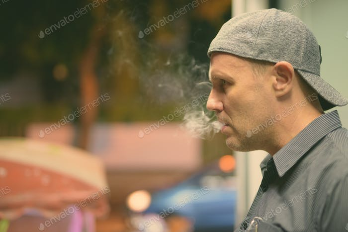Mature man smoking electronic cigarette in the streets at night