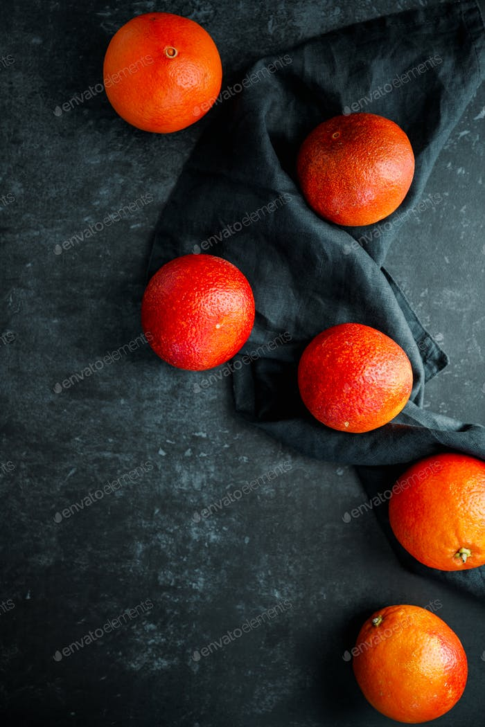 Flat lay food composition with blood oranges on a dark blue background.