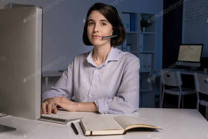 Pretty customer support representative with headset speaking to clients online