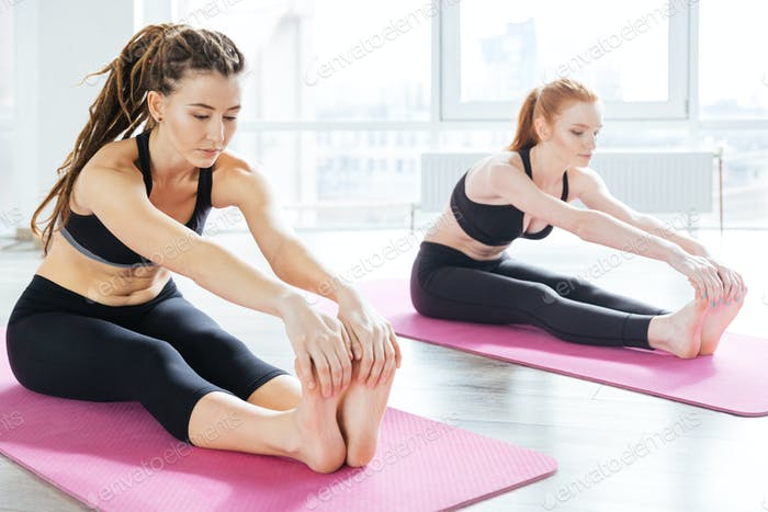 Two concentrated women working out and stretching in yoga center