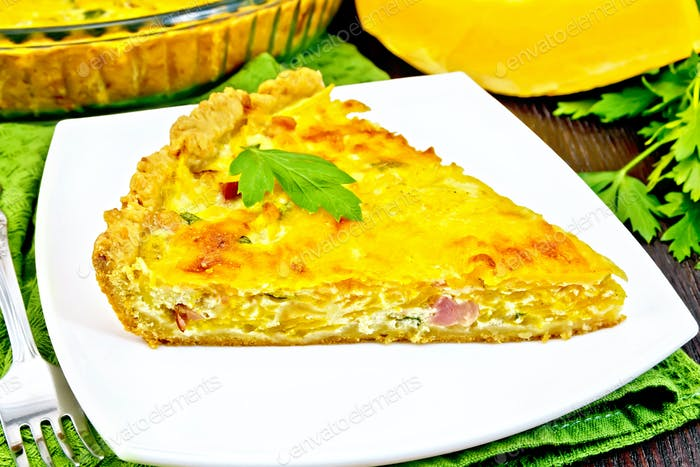 Quiche with pumpkin and bacon in plate on towel