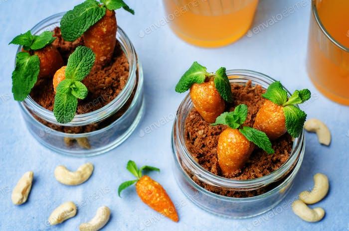 Schokoladenkeks in einem Glas und getrocknete Aprikosen Cashew-Bonbons in Form von Karotten
