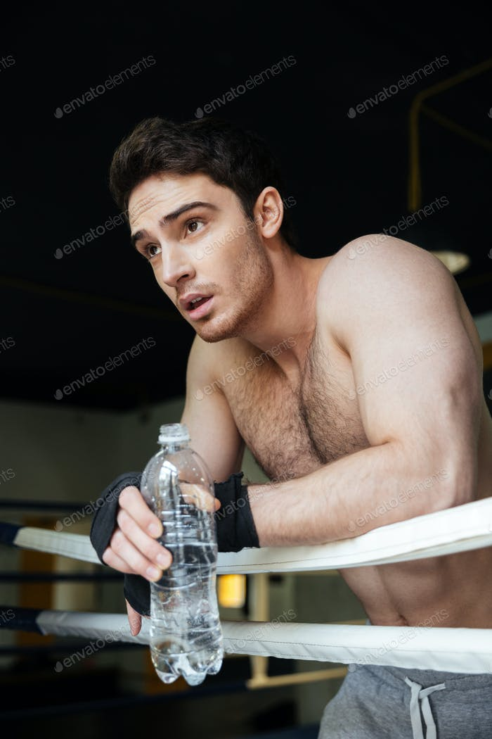Vertical image of young boxer relaxing in boxing ring