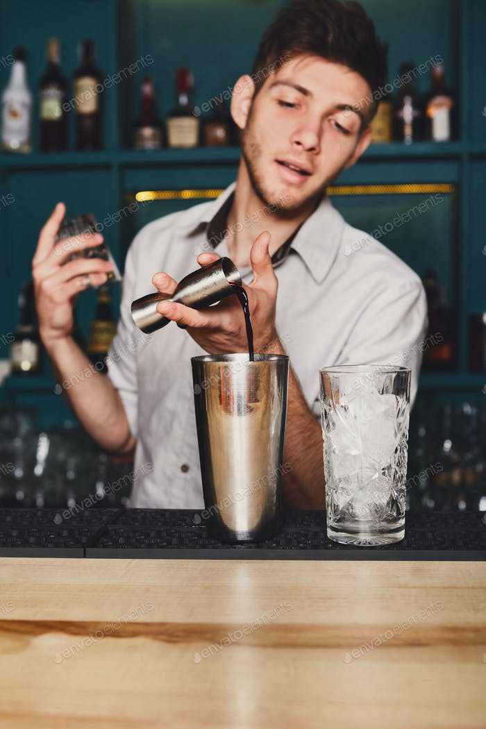 Young handsome barman pouring cocktail drink into glass