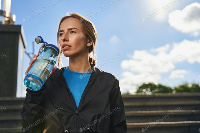 Athletic young woman quenching thirst in city