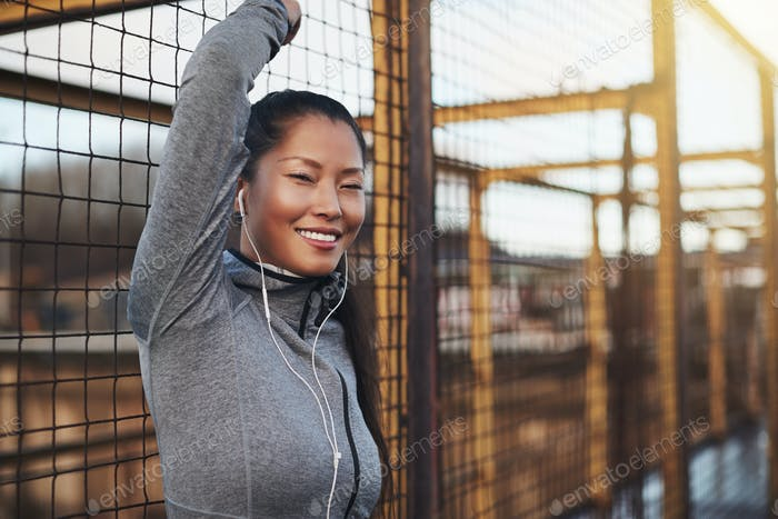 Sporty young Asian woman standing against a mesh wall outside