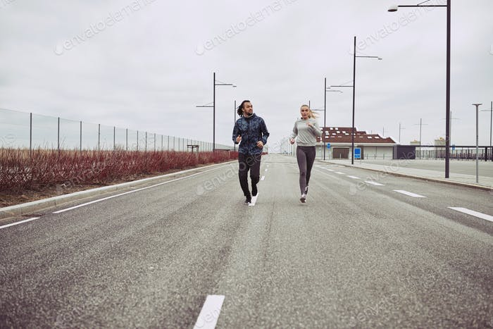 Young couple in sportswear running along a road together
