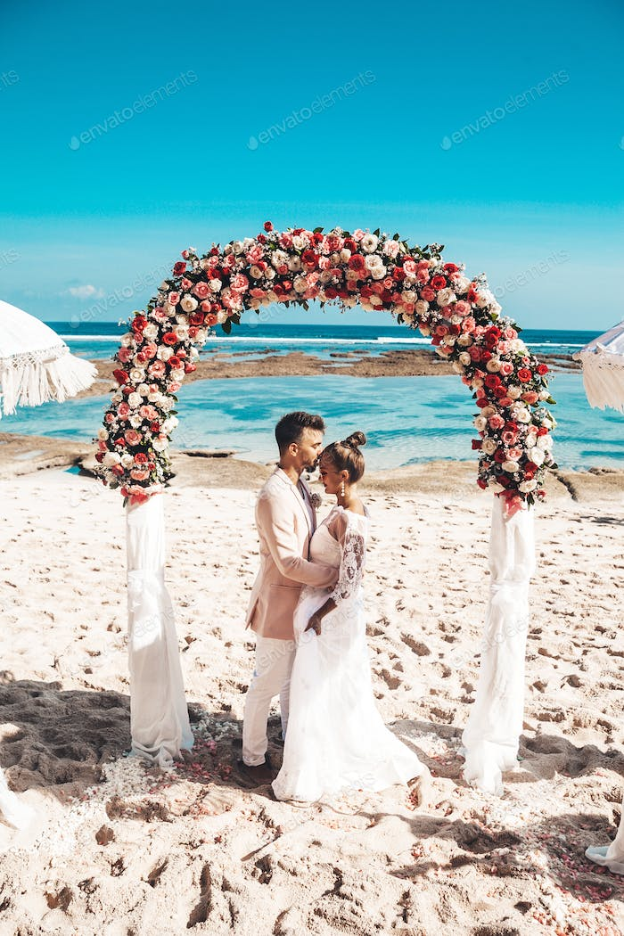 Bride and groom posing at the beach