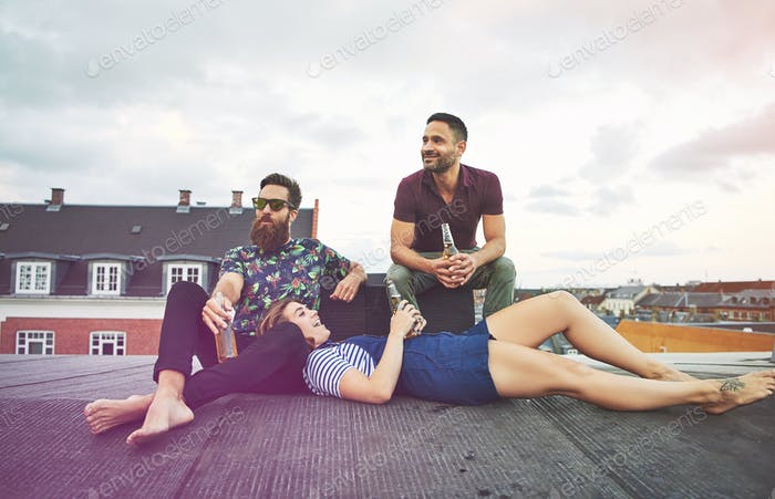 Woman in lap of barefoot man near friend on roof