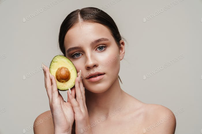 Image of beautiful shirtless woman posing with avocado at camera