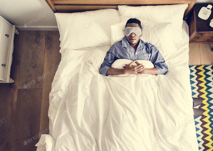 Schwarzer Mann schlafen auf dem Bett mit Augenmaske