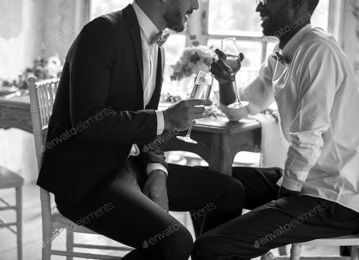 Gay paar sitzen im Gespräch mit Wein Gläser zusammen