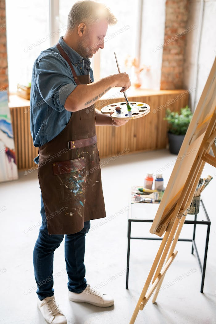 Middle aged painter in casualwear and apron mixing colors on palette
