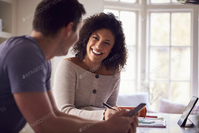 Couple With Digital Tablet Working From Home On Kitchen Counter