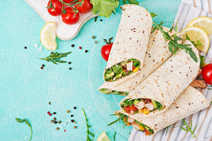 Burritos wraps with chicken and vegetables on light  background.