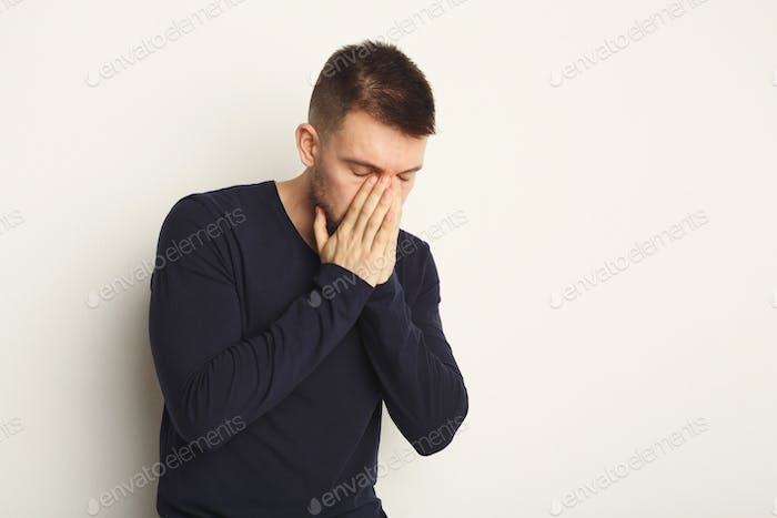 Upset man posing on white background