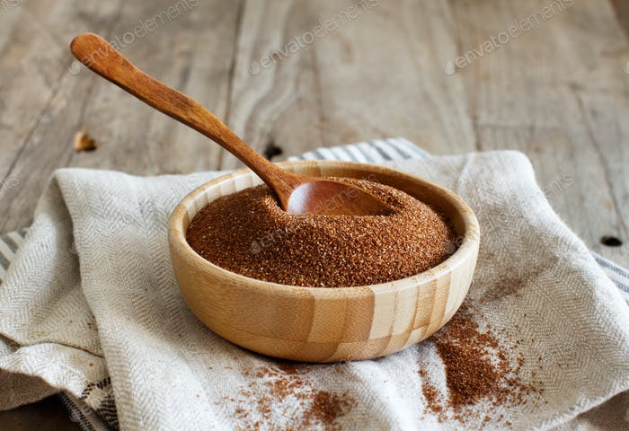 Raw teff grain in a wooden bowl close up