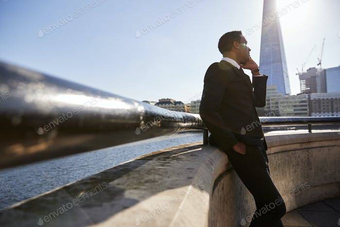 Young black businessman in London,  using smartphone, low angle