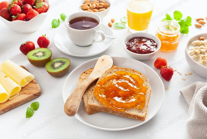 healthy breakfast with toast, strawberry, nuts, jam and tea