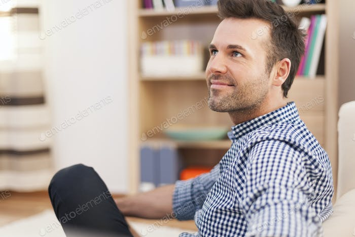 Smiling man sitting on sofa and looking away