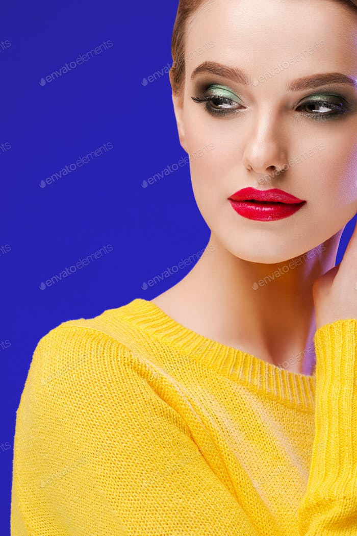 Colorful makeup woman in yellow clothes on color summer background. Studio shot.