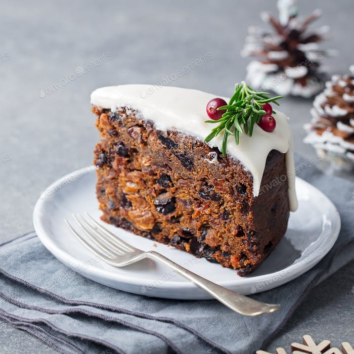 Christmas Fruit Cake, Pudding on White Plate. Traditional New Year Dessert. Close up.