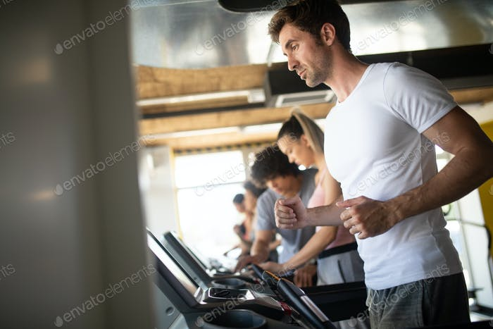 People running on treadmill in gym doing cardio workout