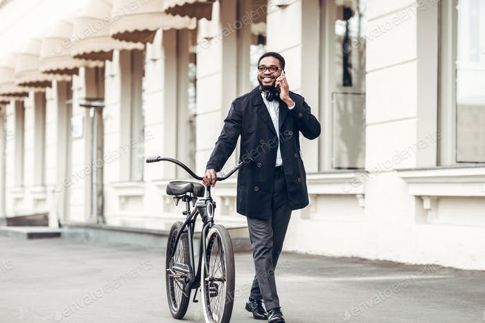 Businessman walking with bicycle and talking on phone