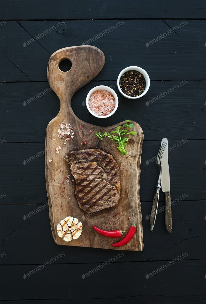 Grilled ribeye beef steak with herbs and spices on walnut cutting board over black wooden background