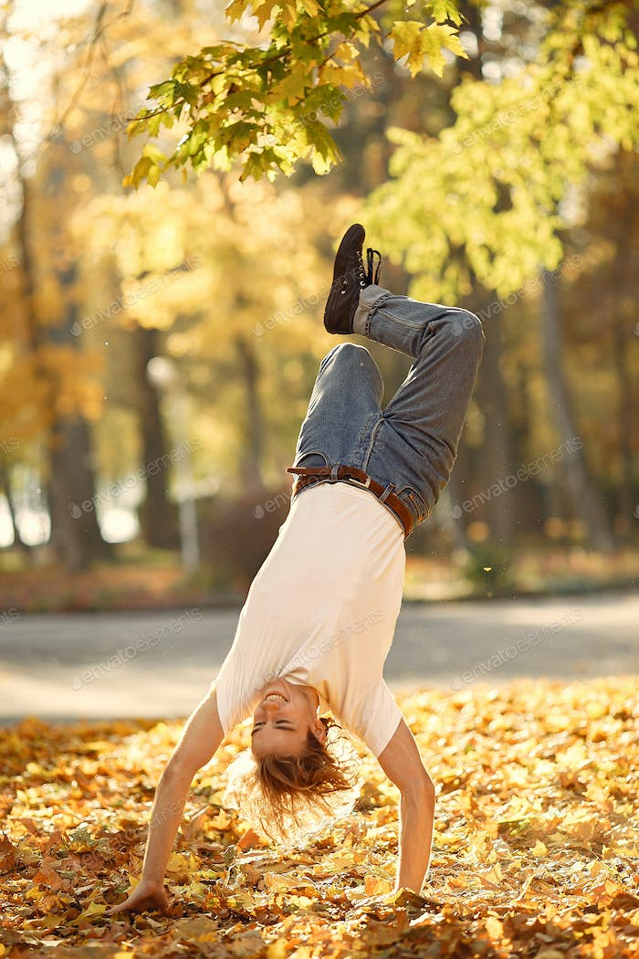 Young casual man dancing outdoor in city park
