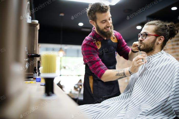 Клиент во время ухода за бородкой и усами в парикмахерской