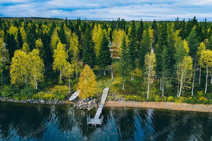 Luftaufsicht der Blockhütte oder Hütte mit Sauna im Frühlingswald am See in Finnland