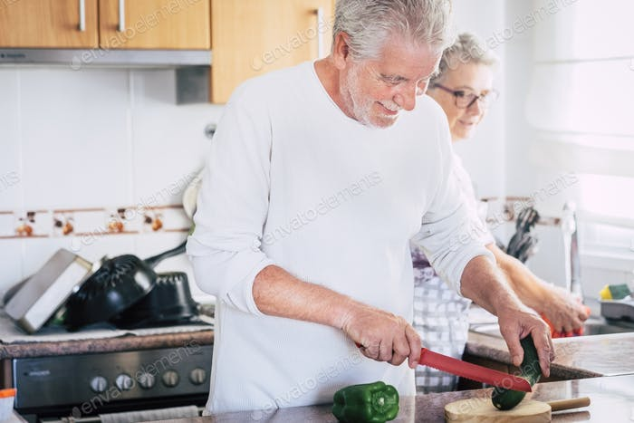 Old couple laughing together - adult man is cooking and smiling