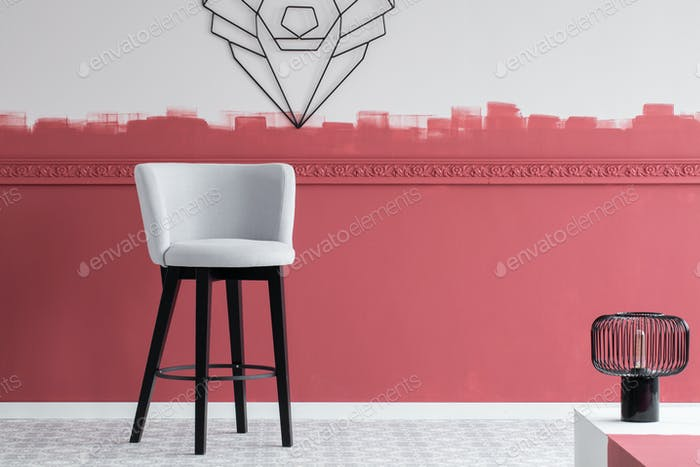 Stylish modern installation on the wall of trendy interior with elegant grey chair