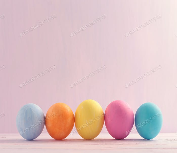 Five multicolored Easter eggs on light background