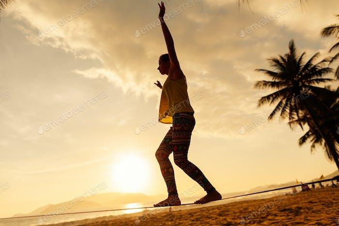 teenager-Mädchen Balancing auf slackline auf die Strand in sunrise silhoutte