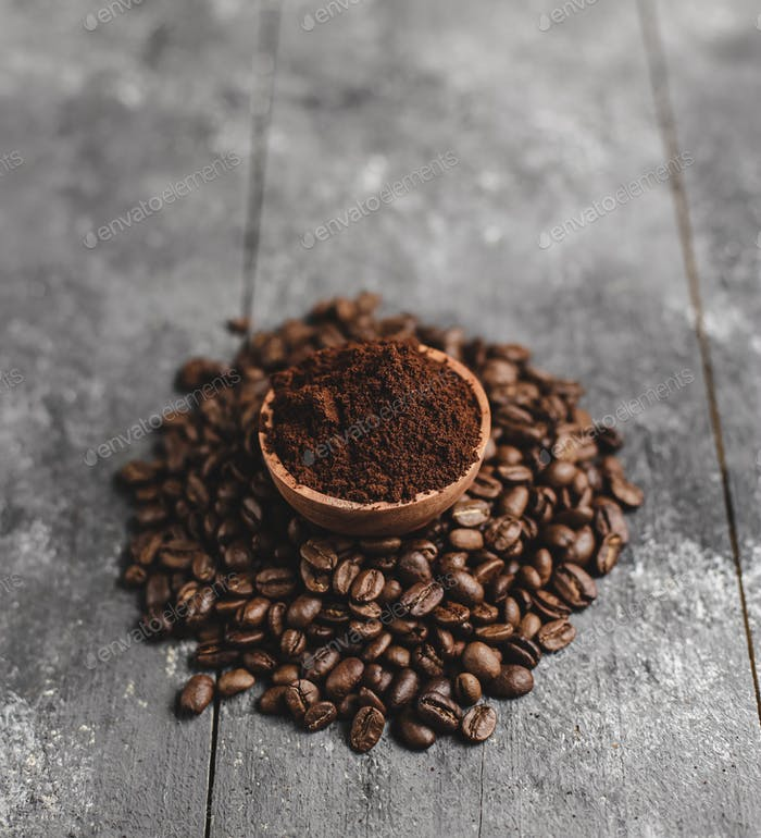 ground coffee in wood saucer with grunge black background
