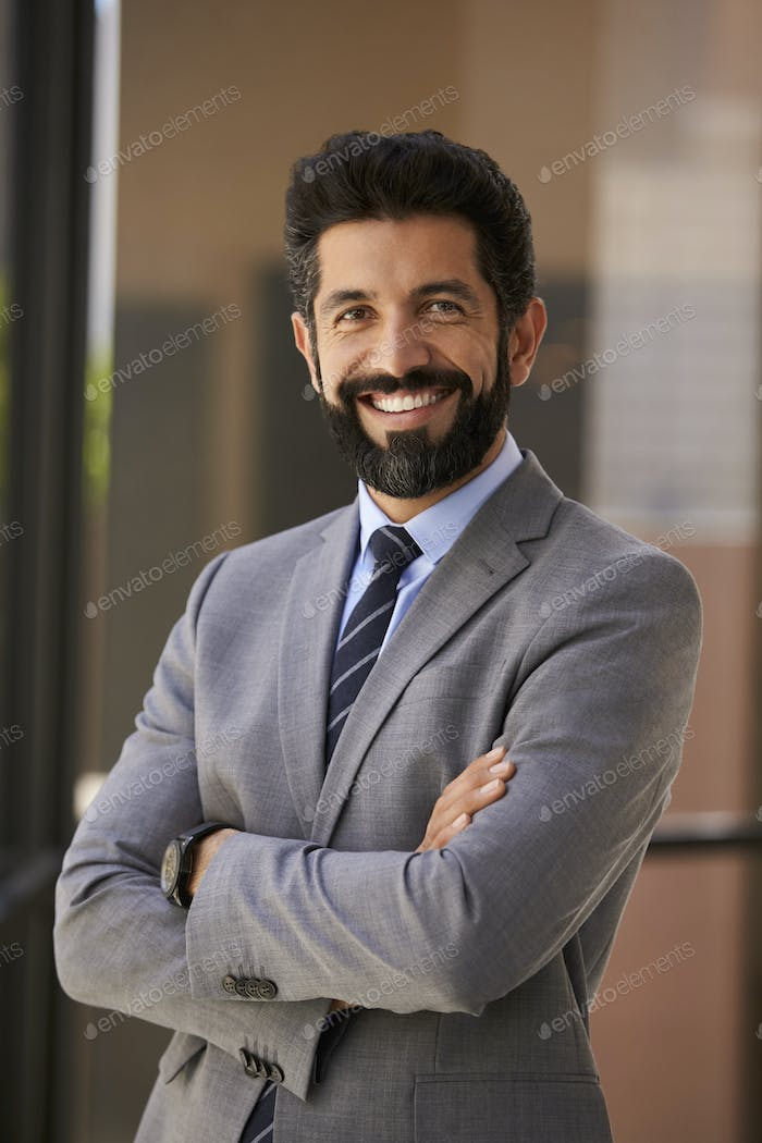 Smiling Hispanic businessman with arms crossed, vertical