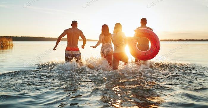 Freunde spritzen Wasser beim Laufen in einen See bei Sonnenuntergang