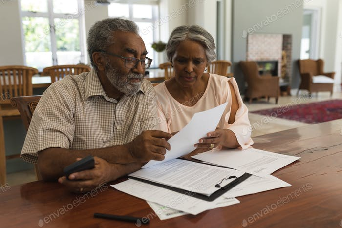 Senior couple discussing over invoices in the living room