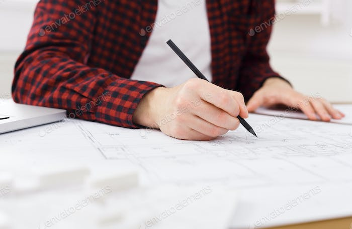 Young architect working with blueprints in the office