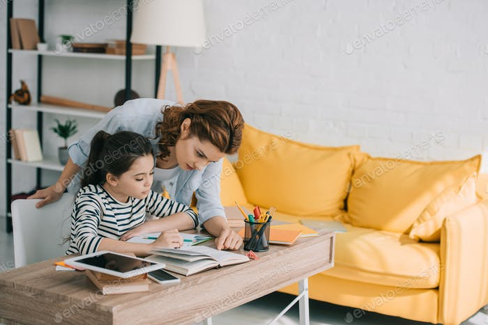 beautiful woman helping adorable daughter doing schoolwork at home