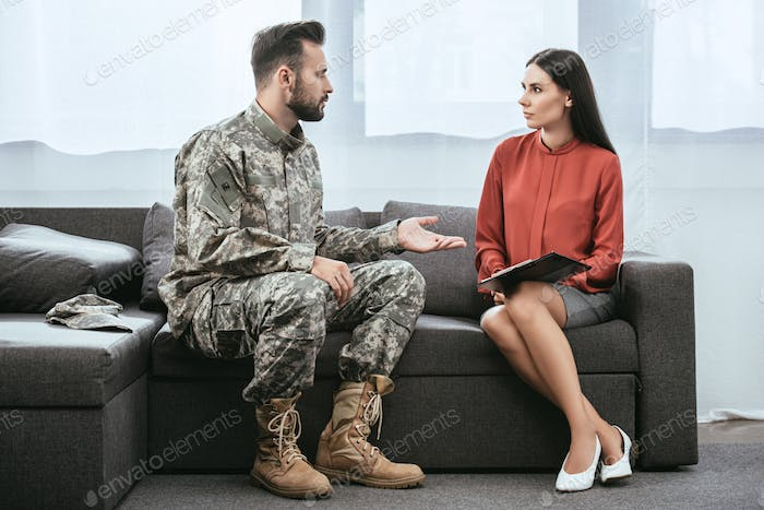 soldier in military uniform with ptsd talking to psychiatrist at therapy session