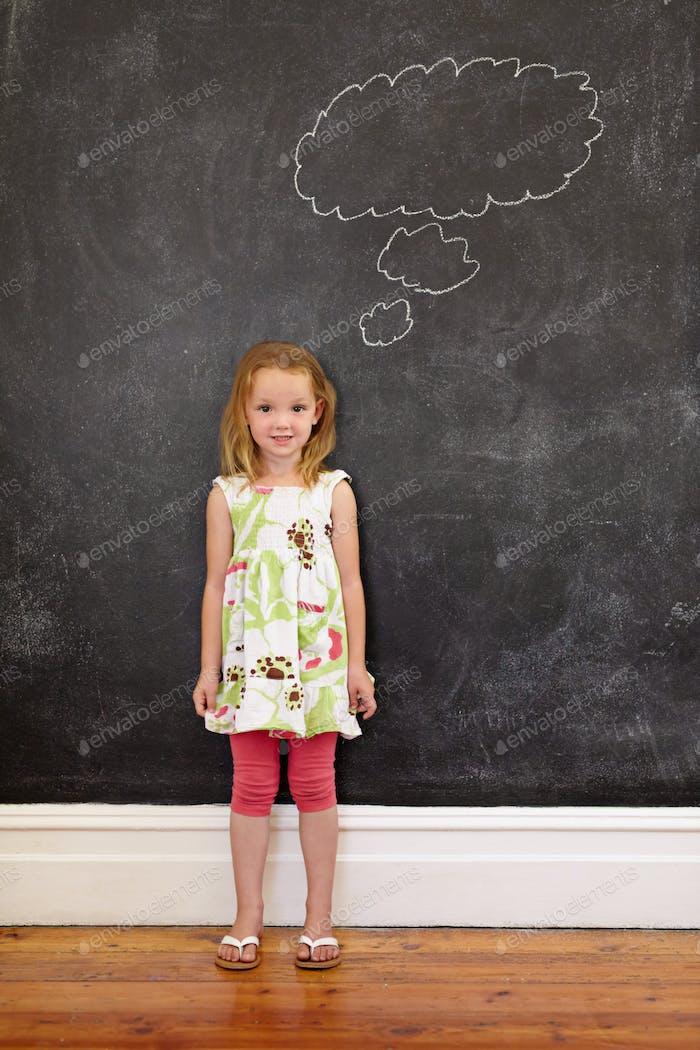 Sweet little girl thinking in front of blackboard