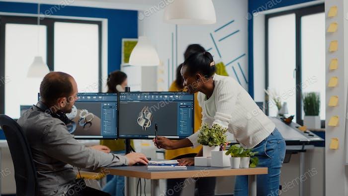Equipo diverso de ingenieros que trabajan en la computadora en el diseño de piezas mecánicas